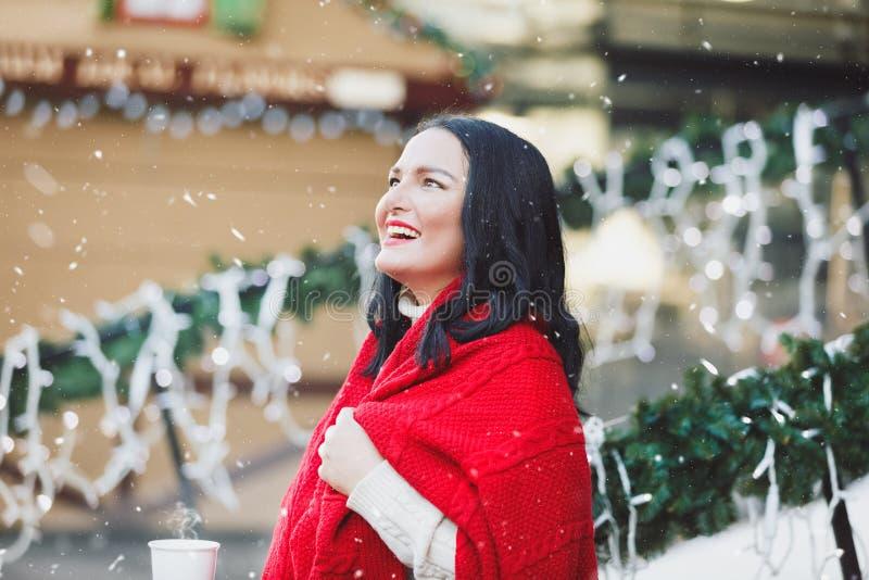 Kobieta stojąca na świątecznym ganku domu z filiżanką gorącego napoju fotografia royalty free