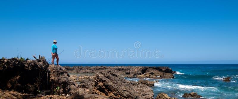 Kobieta stojaki na ska?ach przegapia ocean spokojnego zdjęcie royalty free