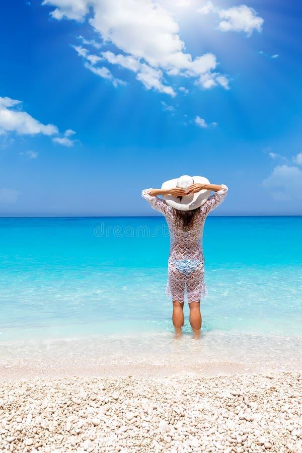 Kobieta stojaki w błękitne wody Grecki morze zdjęcia stock