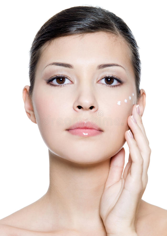 Kobieta stosować kosmetyczną śmietankę na twarzy zdjęcie stock