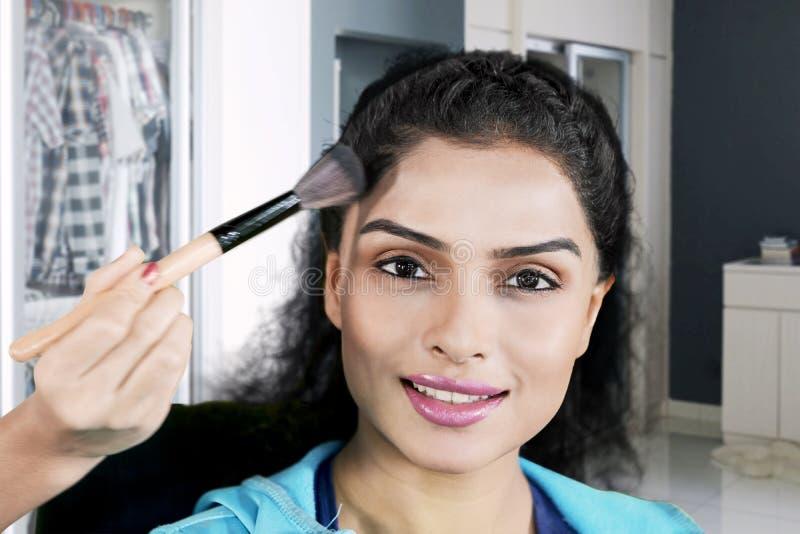 Kobieta stosować proszek jej makeup artystą fotografia stock
