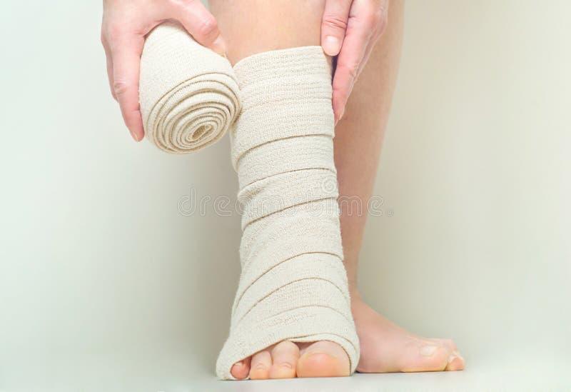 Kobieta stosuje elastycznego uciskowego bandaż jako zakrzepicy zapobieganie po żylakowatej operaci zdjęcia royalty free