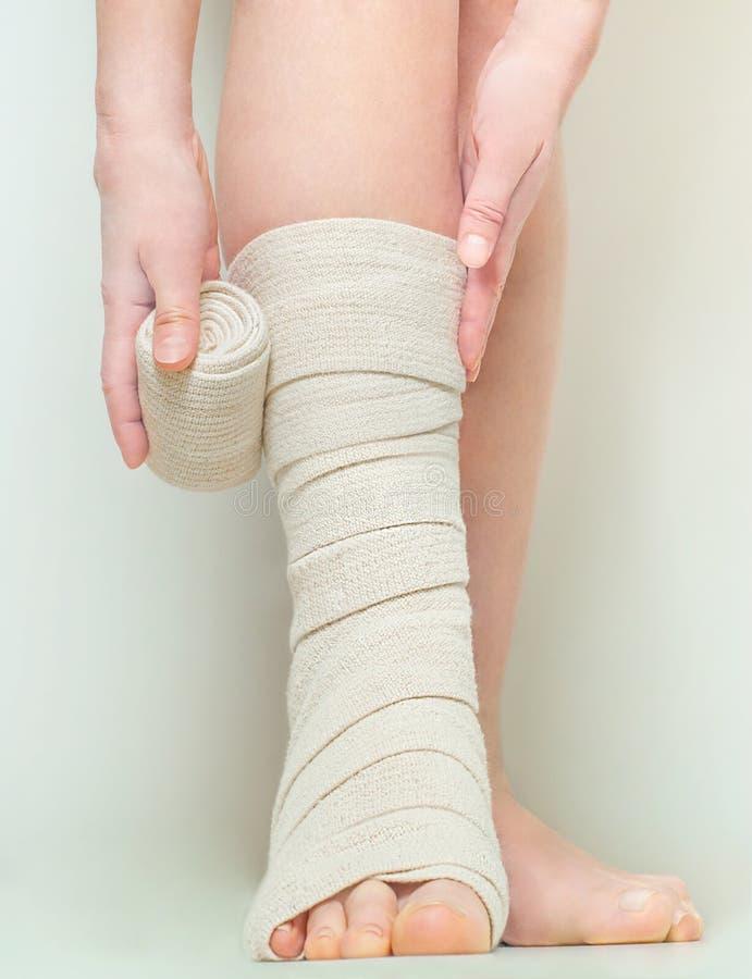 Kobieta stosuje elastycznego uciskowego bandaż jako zakrzepicy zapobieganie po żylakowatej operaci fotografia royalty free