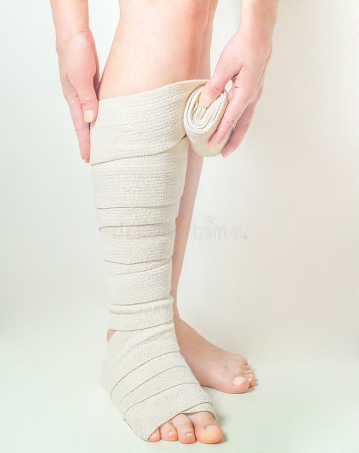 Kobieta stosuje elastycznego uciskowego bandaż jako zakrzepicy zapobieganie po żylakowatej operaci zdjęcie royalty free
