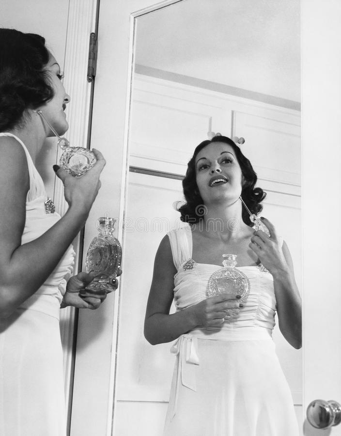 Kobieta stosuje pachnidło przy lustrem (Wszystkie persons przedstawiający no są długiego utrzymania i żadny nieruchomość istnieje zdjęcia stock