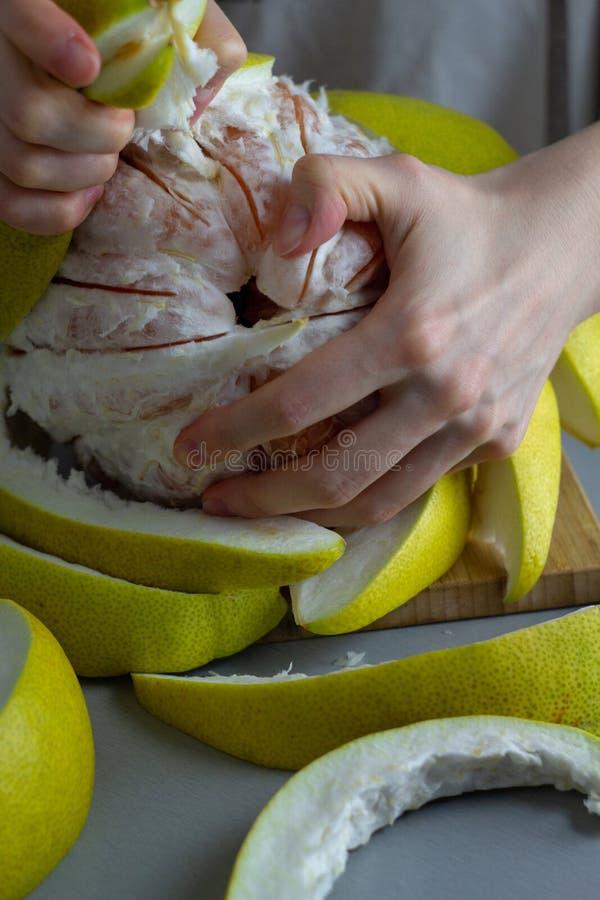 Kobieta struga daleko świeżego czerwonego pomelo rękami na stole zdjęcie stock