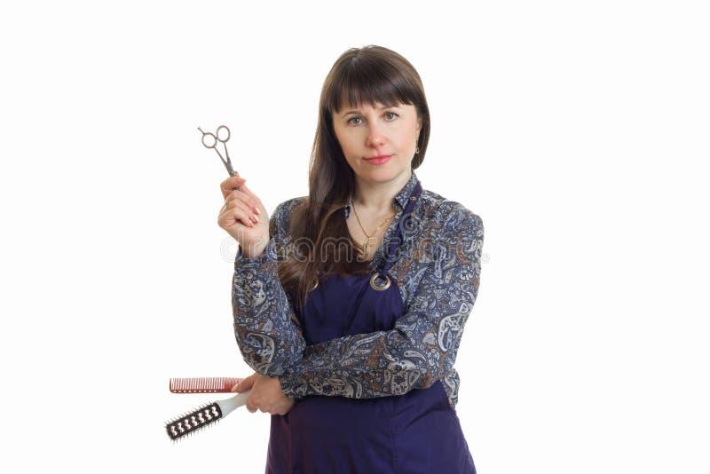Kobieta stylista jest ubranym chwyta narzędzie w rękach i fartucha obraz royalty free