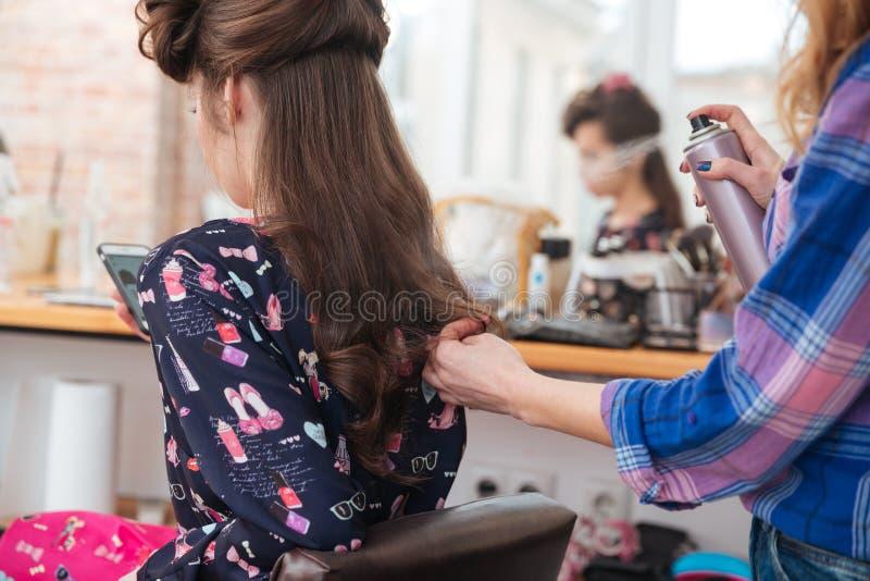 Kobieta stylista stosuje lakier do włosów długie włosy kobieta obrazy royalty free