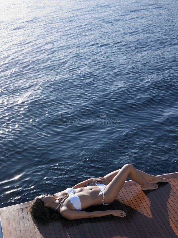 Kobieta Sunbathing Na jachtu Floorboard W bikini zdjęcie royalty free
