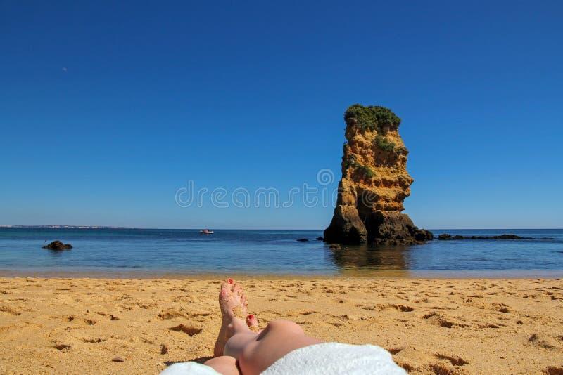 Kobieta suntanned nogi, rockową formację i turkus w tle, zdjęcie stock