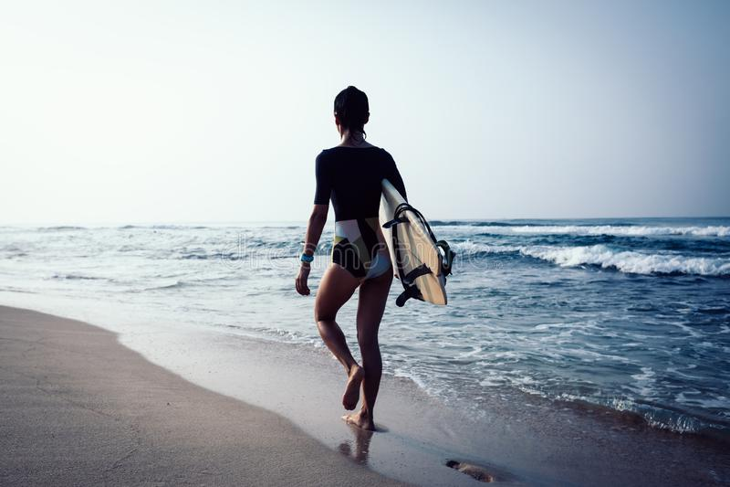 Kobieta surfingowa odprowadzenie z surfboard zdjęcia stock