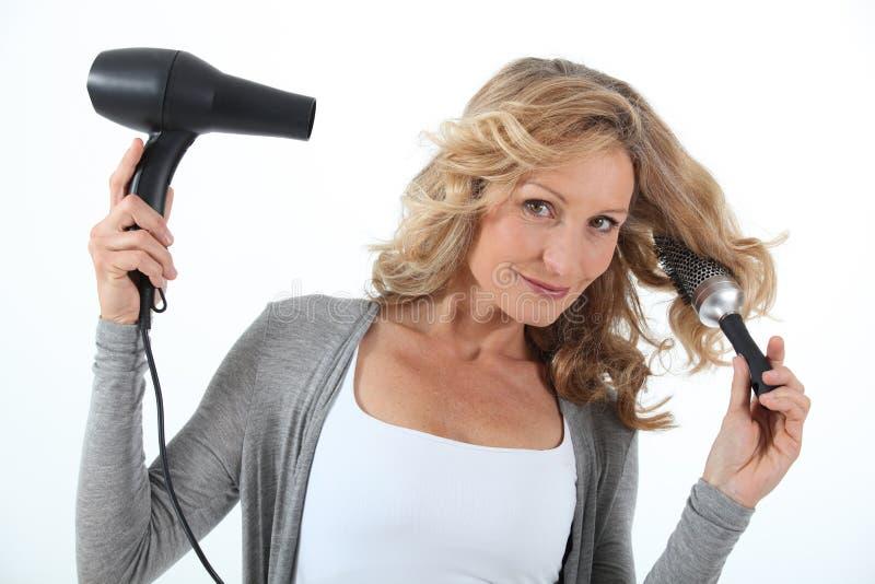 Kobieta suszarniczy włosy zdjęcia stock