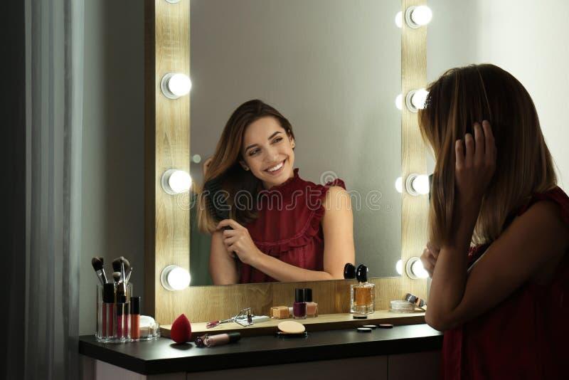 Kobieta szczotkuje włosianego pobliskiego lustro z żarówkami zdjęcia royalty free