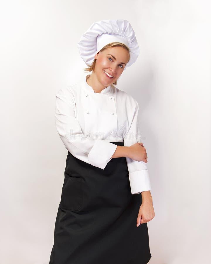 Kobieta szef kuchni ono uśmiecha się nad białym bacground zdjęcia royalty free