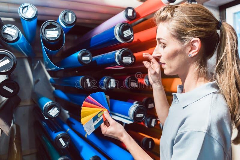 Kobieta szuka prawego ekranowego kolor w reklamowej materialnej produkcji obraz stock