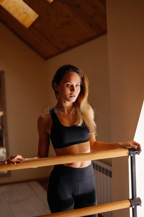 Kobieta tancerz pozuje blisko barre w baletniczym studiu obrazy royalty free