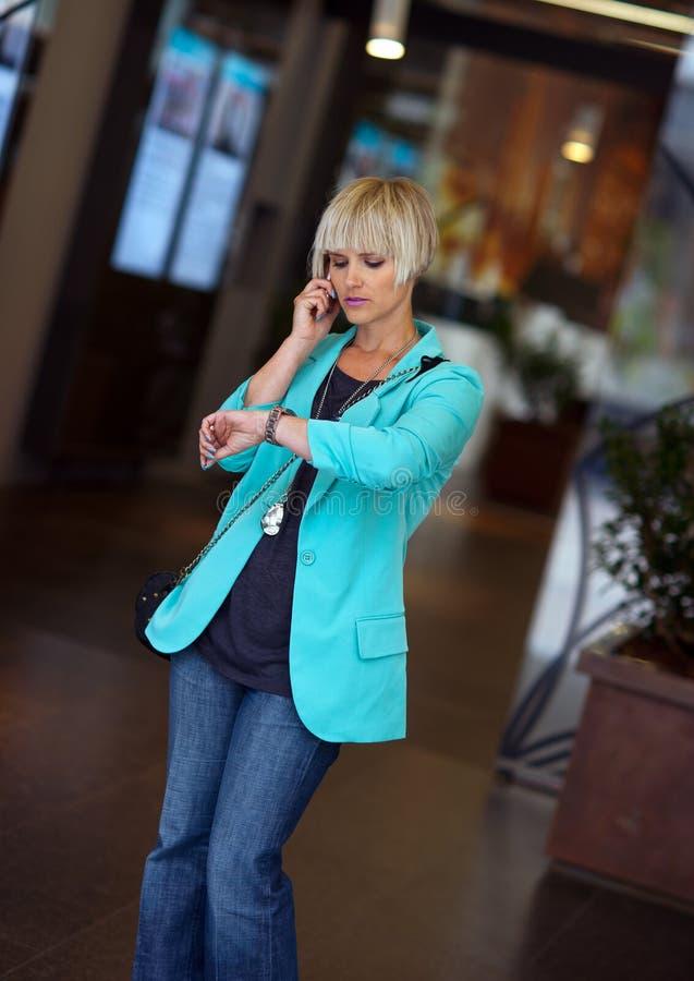 Kobieta target802_0_ przy jej zegarek na ulicie obrazy royalty free