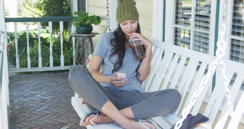 Kobieta texting herbaty na ganeczku i pije fotografia stock