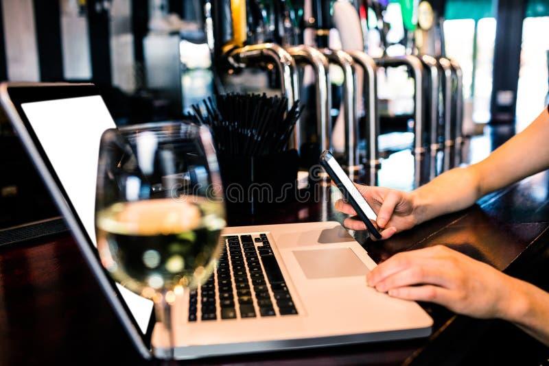 Kobieta texting laptop z winem i używa obraz stock