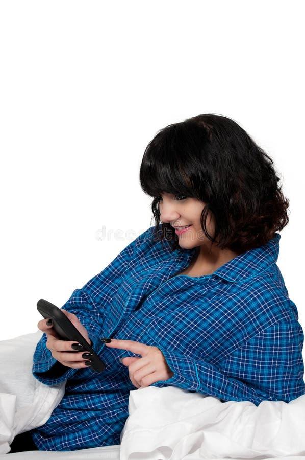 Kobieta Texting w łóżku fotografia royalty free