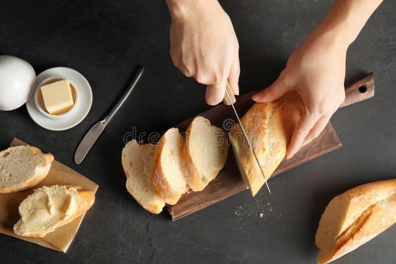 Kobieta tnący chleb na czarnym tle zdjęcie stock