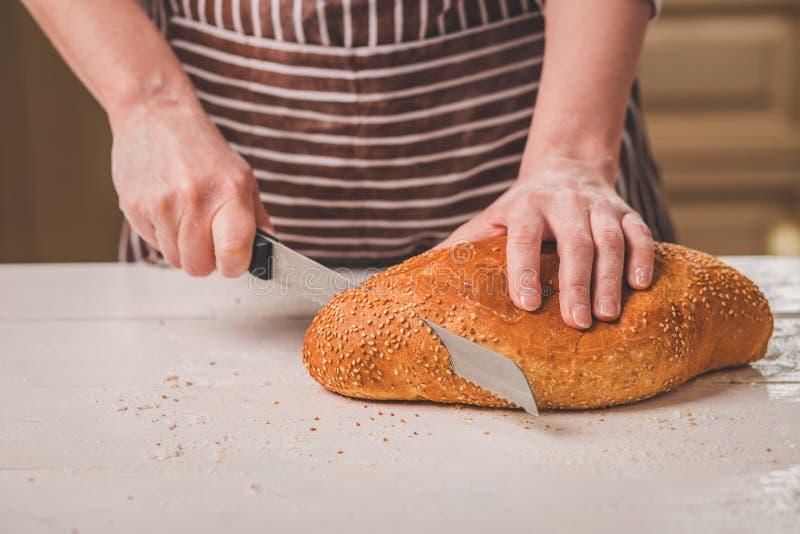 Kobieta tnący chleb na drewnianej desce bakehouse Chlebowa produkcja fotografia stock