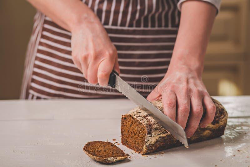 Kobieta tnący chleb na drewnianej desce bakehouse Chlebowa produkcja obraz stock