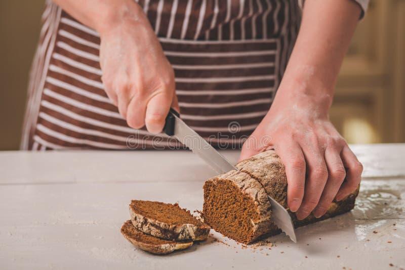 Kobieta tnący chleb na drewnianej desce bakehouse Chlebowa produkcja obraz royalty free