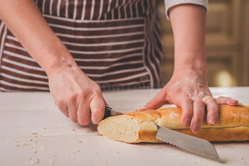 Kobieta tnący chleb na drewnianej desce bakehouse Chlebowa produkcja obrazy stock