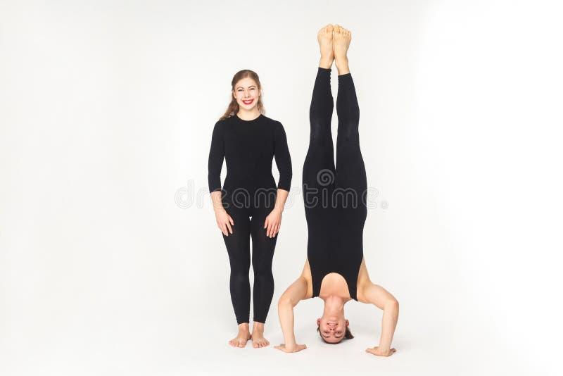 Kobieta toothy uśmiech, stoi blisko mężczyzna stojaka na głowie fotografia royalty free