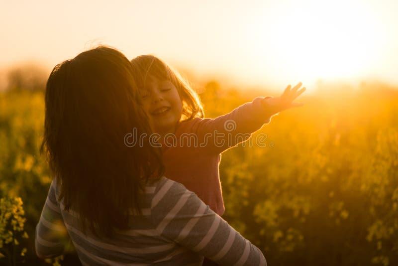 Kobieta trzyma ślicznego uśmiechniętego beztroskiego dziewczyny dziecka i obszycie oddalony obraz royalty free