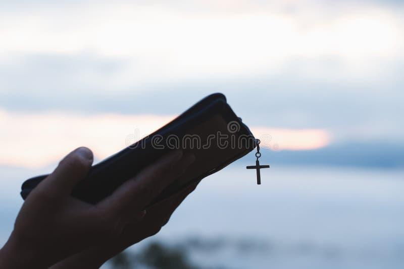 Kobieta trzyma świętą biblię w ona i ono modli się w ranku ręki Ręki składali w modlitwie na Świętej biblii w kościelnym pojęciu obrazy royalty free