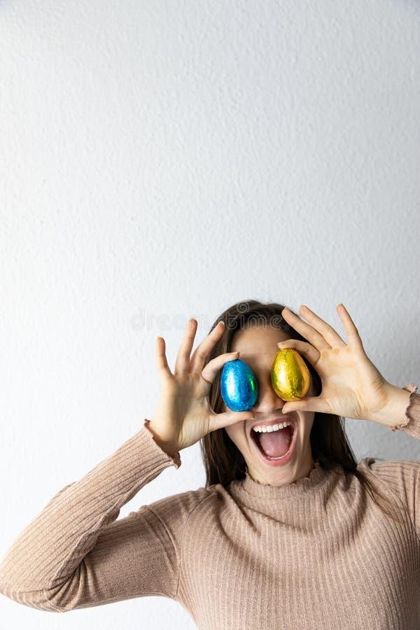 Kobieta trzyma b??kitnych i z?otych czekoladowych Easter jajka przed jej oczami obrazy stock