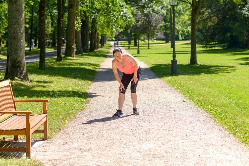 Kobieta trzyma bolesnego kolano w parku fotografia royalty free