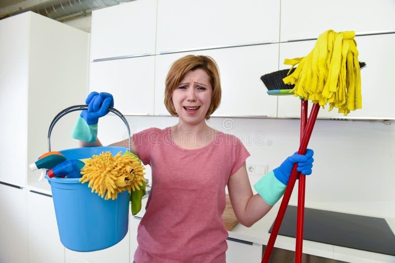 Kobieta trzyma cleaning z czerwonym włosy w gumowych płuczkowych rękawiczkach forsuje kwacz i miotłę zdjęcia royalty free