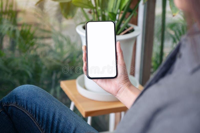 Kobieta trzyma czarnego telefon komórkowego z pustym desktop ekranem i używa w kawiarni zdjęcia stock