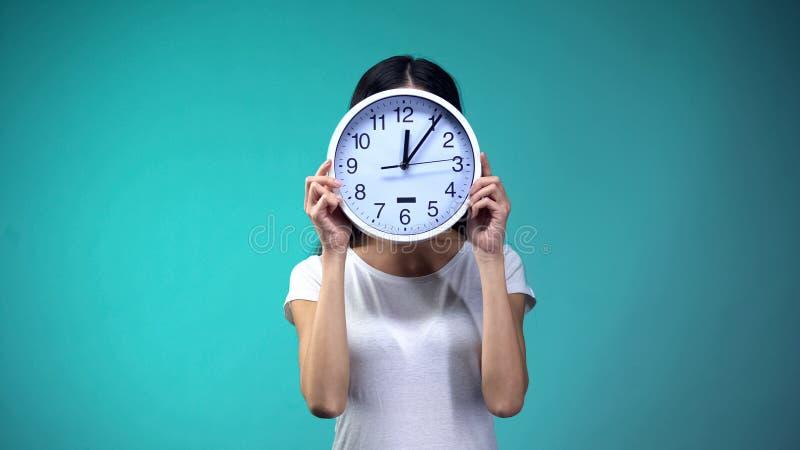 Kobieta trzyma du?ego zegar przed jej twarz?, czasu zarz?dzaniem i rutyn?, ostateczny termin zdjęcia royalty free