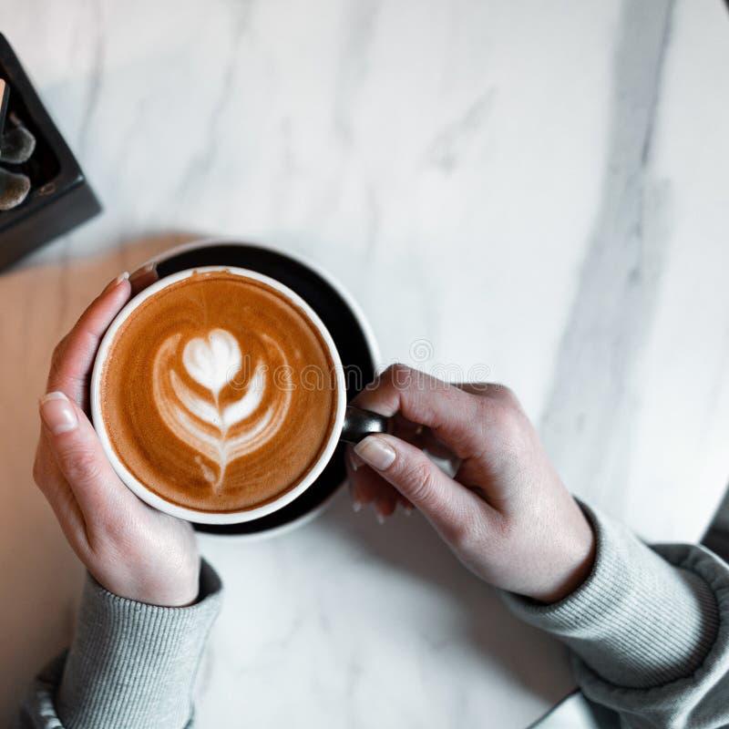 Kobieta trzyma filiżankę z wyśmienicie gorącym latte w rocznika sklepie z kawą Kawowy smakosz antykwarska kawa umowy gospodarczej fotografia royalty free