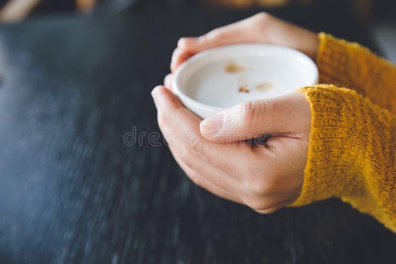 Kobieta trzyma filiżankę gorąca kawa w ciepłym pulowerze z kubkiem obrazy stock