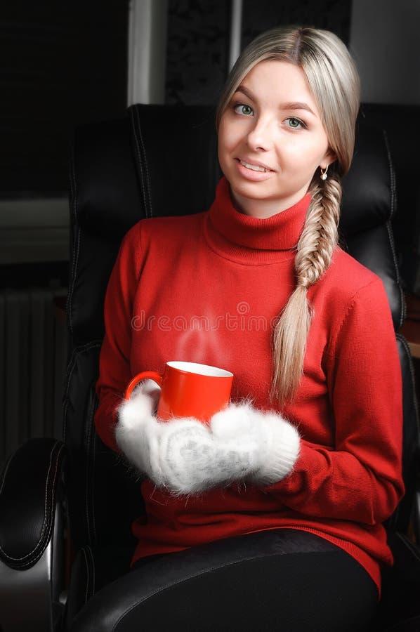 Kobieta trzyma filiżankę w czerwonym pulowerze i białych mitynkach obraz stock