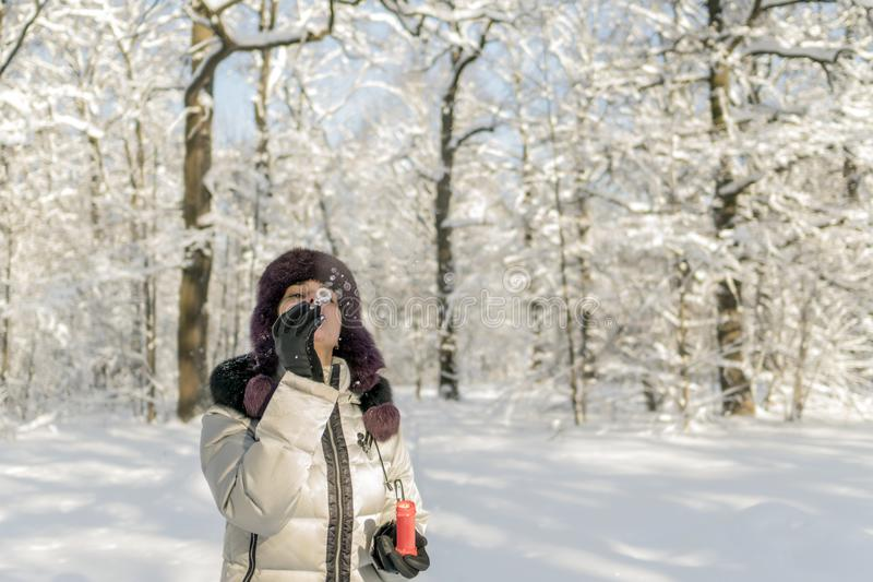 Kobieta trzyma garść śnieg w ona ręki i ciosy na nim Wi zdjęcie stock