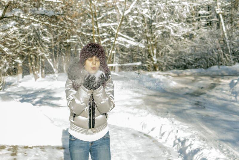 Kobieta trzyma garść śnieg w ona ręki i ciosy na nim Wi obrazy stock