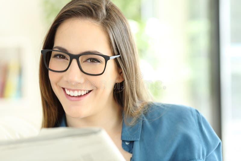Kobieta trzyma gazetę jest ubranym eyeglasses patrzeje ciebie zdjęcia royalty free