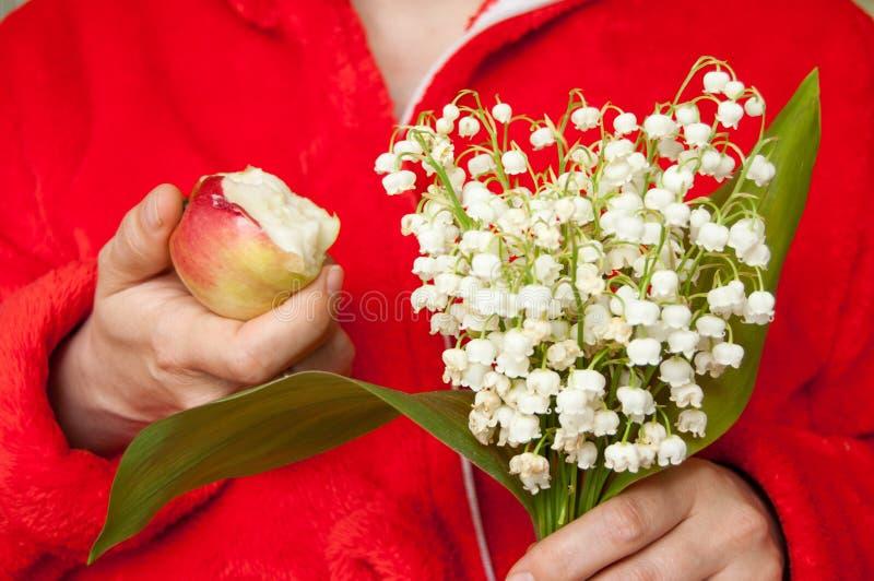 Kobieta trzyma gryźć jabłka w jeden ręce w czerwonym kontuszu, bukiet leluja dolina w inny ręka obrazy royalty free