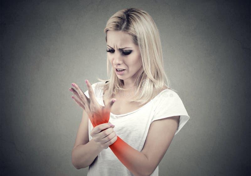 Kobieta trzyma jej bolesną nadgarstku zwichnięcia bólu lokację wskazująca czerwonym punktem fotografia stock