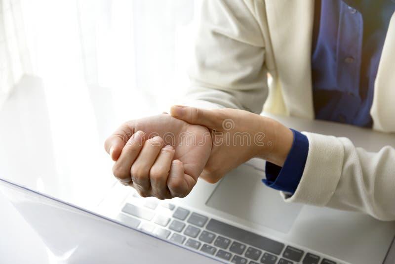 Kobieta trzyma jej nadgarstku ból od używać komputer obrazy stock