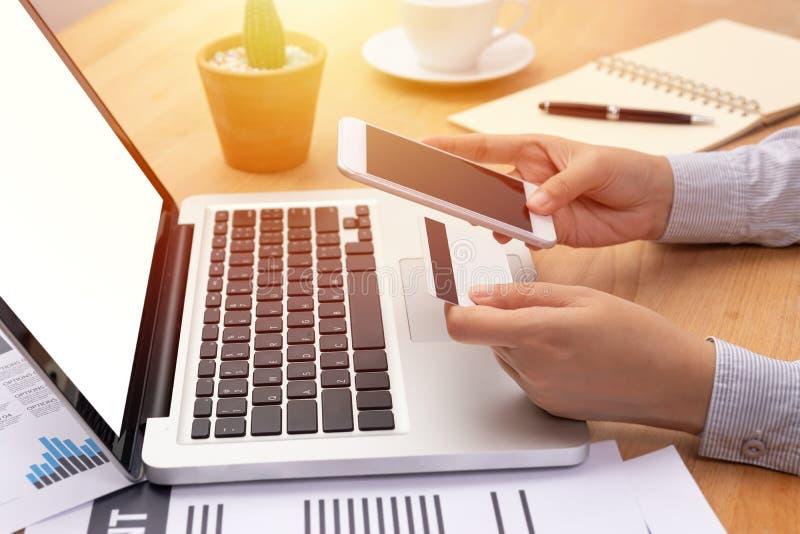 Kobieta trzyma kartę kredytową robi online zapłacie przez mobilnego smartphone z pustym ekranem przed komputerem zakup i obrazy stock