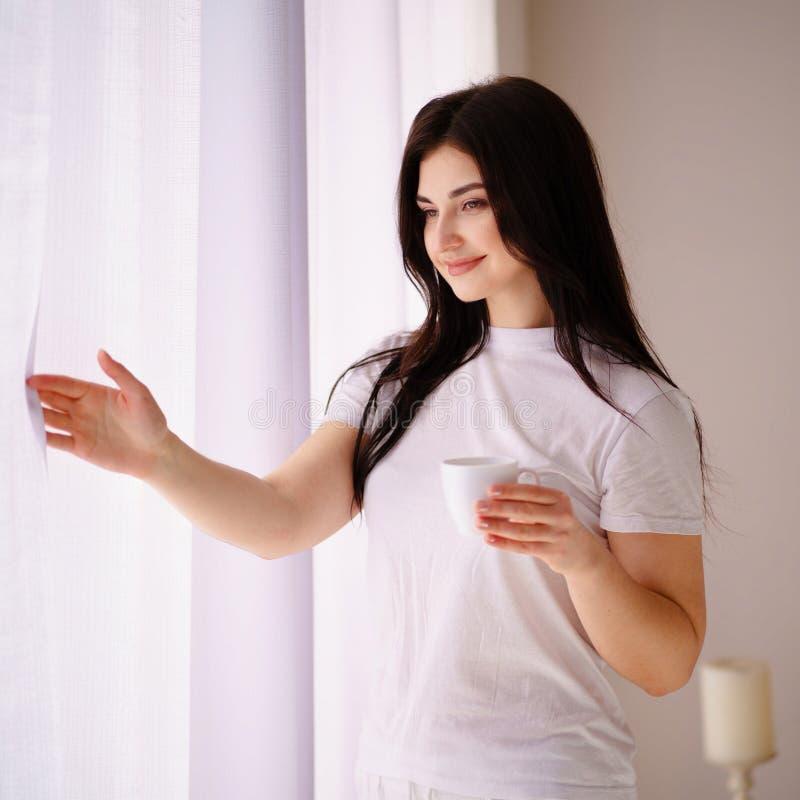Kobieta trzyma kawowego kubek w domu pi?kna nad ptak chmur kolory muchy z?ota charakter wcze?nie rano zwi?ksza morza przyjemny ci zdjęcie stock
