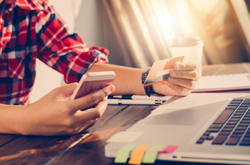 Kobieta trzyma kredytowe karty i telefony komórkowych robi zakupy obraz stock