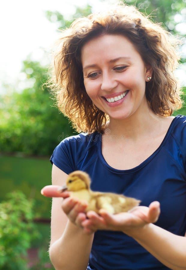 Kobieta trzyma małego żółtego kaczątka w ona ręki zdjęcie royalty free